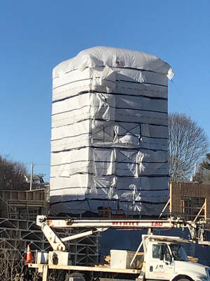 Elevator tower wrapped in building wrap